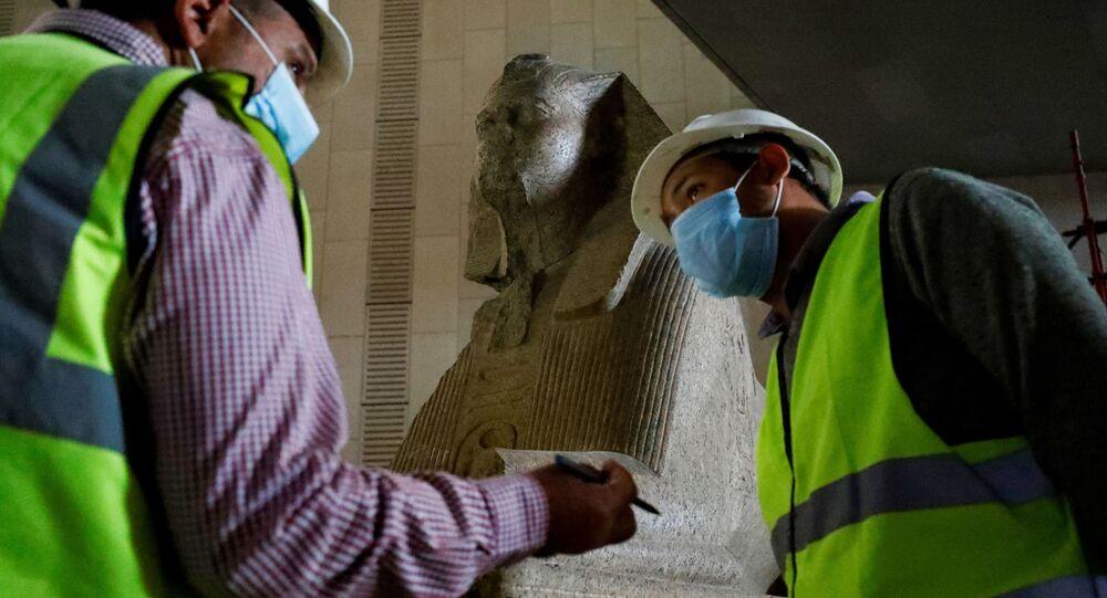 موظفون يرتدون كمامات طبية لتفادي الإصابة بفيروس كورونا  في المتحف المصري الكبير، الذي شيد حديثا في الجيزة بضواحي  القاهرة ، 13 أبريل 2020.