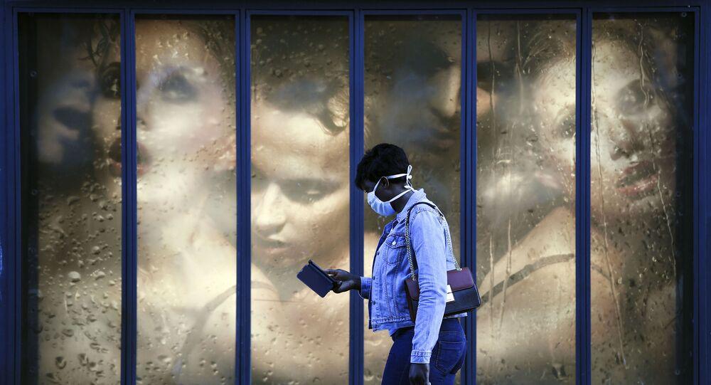 امرأة ترتدي كمامة طبية تمر بجوار نافذة متجر في باريس في 14 أبريل 2020، في اليوم التاسع والعشرين من الحجر الصحي المعلن في فرنسا، في إطار الاجراءات الوقائية لمنع انتشار فيروس كورونا (اوفيد-19).