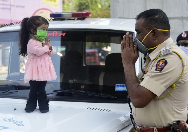 أصغر امرأة في العالم، جيوتي أمجي، ترتدي كمامة طبية وتحي شرطي في ناجبور  13 أبريل 2020، في إطار الاجراءات الوقائية لمنع انتشار فيروس كورونا (اوفيد-19) في الهند