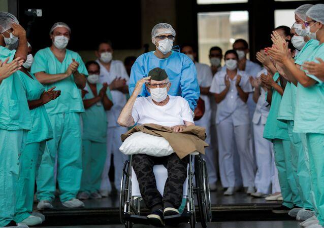 أحد المحاربي القدامى  والمشارك في الحرب العالمية الثانية، البرازيلي، إيرماندو أرميلينو بيفيتا، البالغ من العمر 99 عاماً، يغادر مستشفى القوات المسلحة بعد أن تلقى العلاج من مرض فيروس كورونا (كوفيد-19)، البرازيل، 14 أبريل / نيسان 2020.