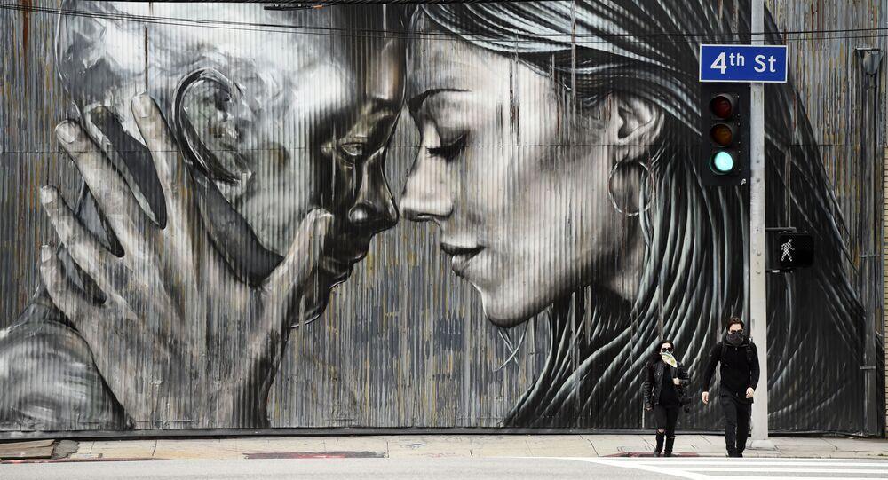 أشخاص يرتدون الكمامات وهم يعبرون الشارع أمام جدارية في حي الفنون في لوس أنجلوس، حيث تستمر أوامر البقاء في المنزل في كاليفورنيا بسبب الفيروس التاجي كورونا، 10 أبريل 2020.