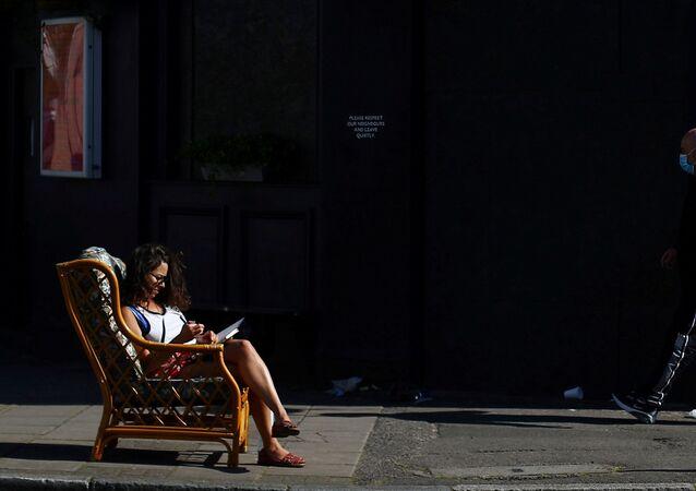 امرأة تجلس في الخارج في  حي داتسون، على خلفية انتشار مرض فيروس كورونا (كوفيد-19)، لندن، بريطانيا، 14 أبريل 2020.