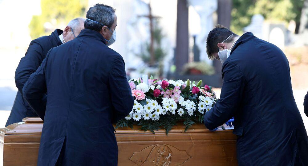عمال المقبرة وموظفو خدمة الجنازات ينقلون تابوت شخص توفي بسبب فيروس كورونا في بيرغامو، إيطاليا
