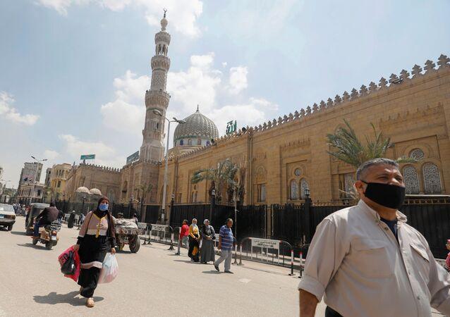 رجل يرتدي كمامة واقية من فيروس كورونا يسير أمام مسجد السيدة زينب المغلق