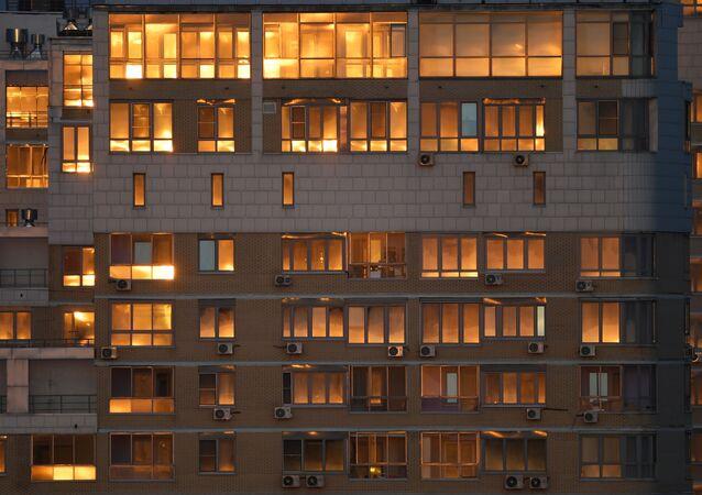 أشعة غروب الشمس تنعكس على نوافذ المنازل، حيث يبقى المواطنون معظم الوقت في إطار العزل الصحي