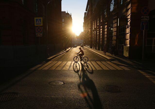 راكب دراجة هوائية يعبر شارع غالوتفينسكي على خلفية غروب الشمس في موسكو