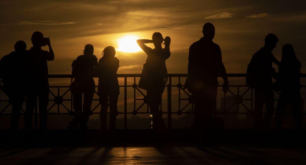 أشخاص في ساحة المشاهدة، أمام مبنى المعهد الروسي للعلوم على خلفية غروب الشمس