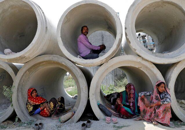 عمال مهاجرون يستريحون في أنابيب إسمنتية، خلال الإغلاق التام على مستوى الدولة، لإبطاء انتشار مرض فيروس كورونا (كوفيد-19) في لكناو، الهند ، 22 أبريل 2020.