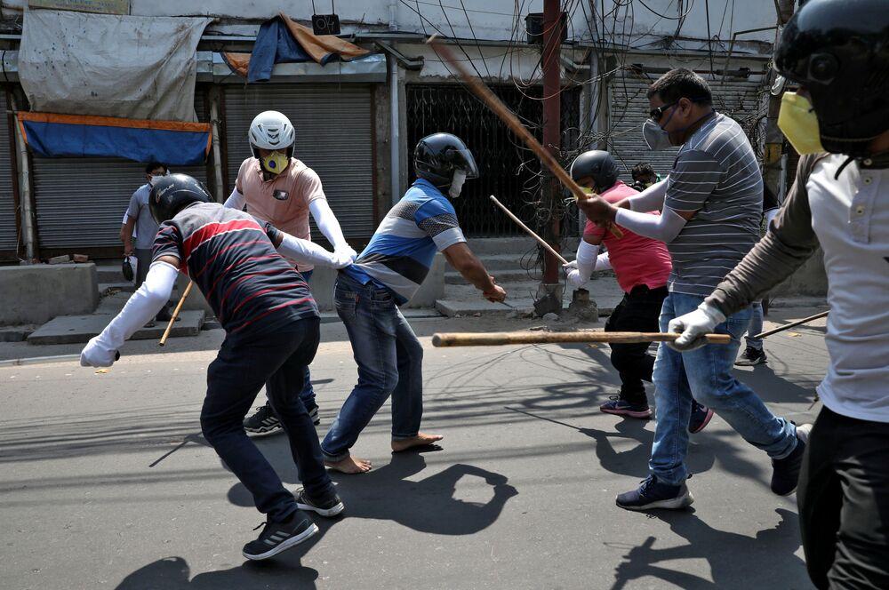 يرتدي رجال الشرطة ملابس مدنية ويستخدمون هراواتهم ضد أشخاص يتحدون الإغلاق التام المفروض من قبل الحكومة لإبطاء انتشار مرض فيروس التاجي (كوفيد-19) في - على مشارف كولكاتا، الهند ، 19 أبريل 2020.
