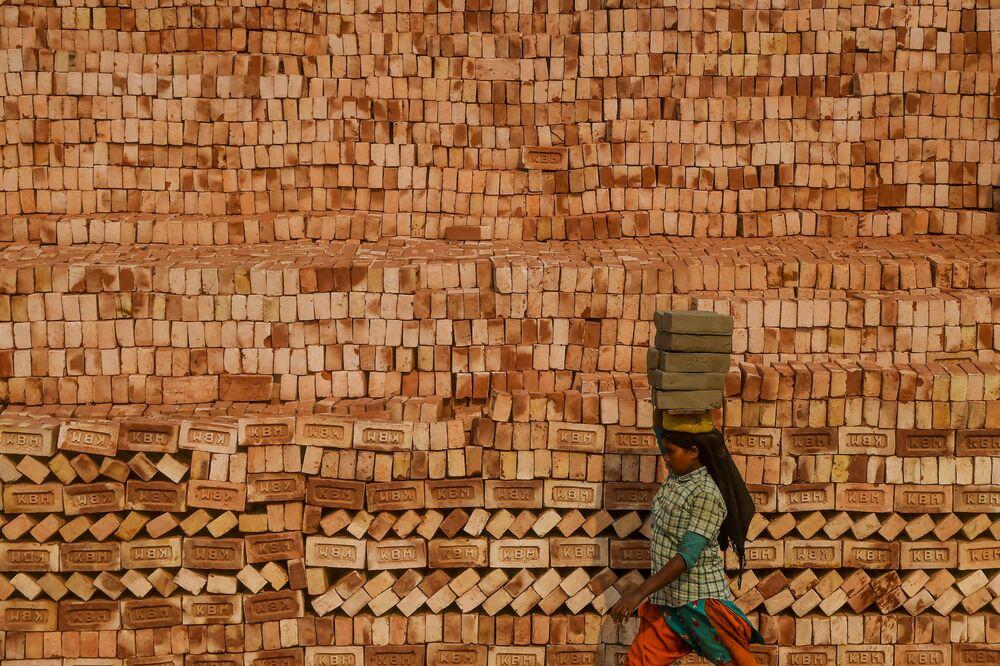 عاملة مهاجرة تحمل الطوب على رأسها أثناء العمل في مصنع قمائن الطوب أثناء إغلاق وطني فرضته الحكومة كإجراء وقائي ضد الفيروس التاجي كوفيد-19، في ضواحي كولكاتا في 18 أبريل 2020.