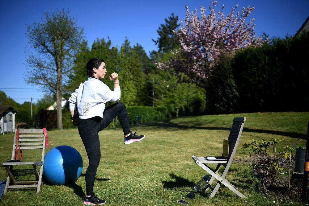 مدربة اللياقة البدنية غابرييل فريسيرا تلقي درسًا عبر الإنترنت في سان ريمي هونور، غرب باريس، 15 أبريل 2020 ، في اليوم الثلاثين من الإغلاق الصارم في فرنسا بهدف كبح انتشار جائحة كوفيد-19، التي يسببه الفيروس التاجي الجديدة.