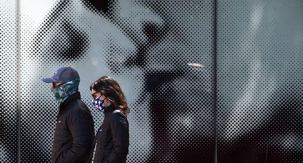 ثنائي يرتدي كمامات واقية يسيران على خلفية لوحة إعلانية لدار السينما، وسط جائحة فيروس كورونا في واشنطن العاصمة، في 22 أبريل 2020.