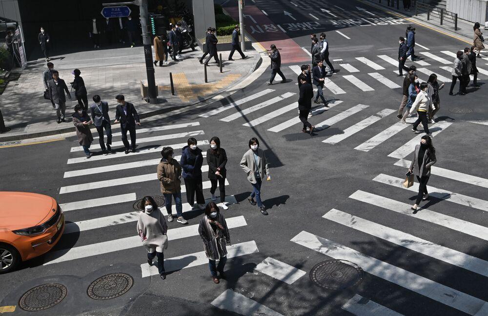 أشخاص مقنعون يعبرون مفترق طرق عند معابر المشاة في سئول، كوريا الجنوبية  23 أبريل 2020