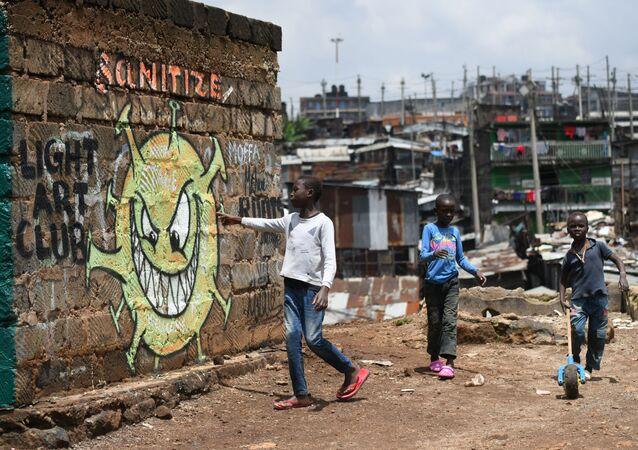 طفل صغير يقرأ الرسالة من لوحة جدارية توعوية تحذر الناس من خطر مرض كوفيد-19 الذي يسببه الفيروس كورونا، في حي وادي ماثاري في نيروبي، كينيا 22 أبريل 2020.