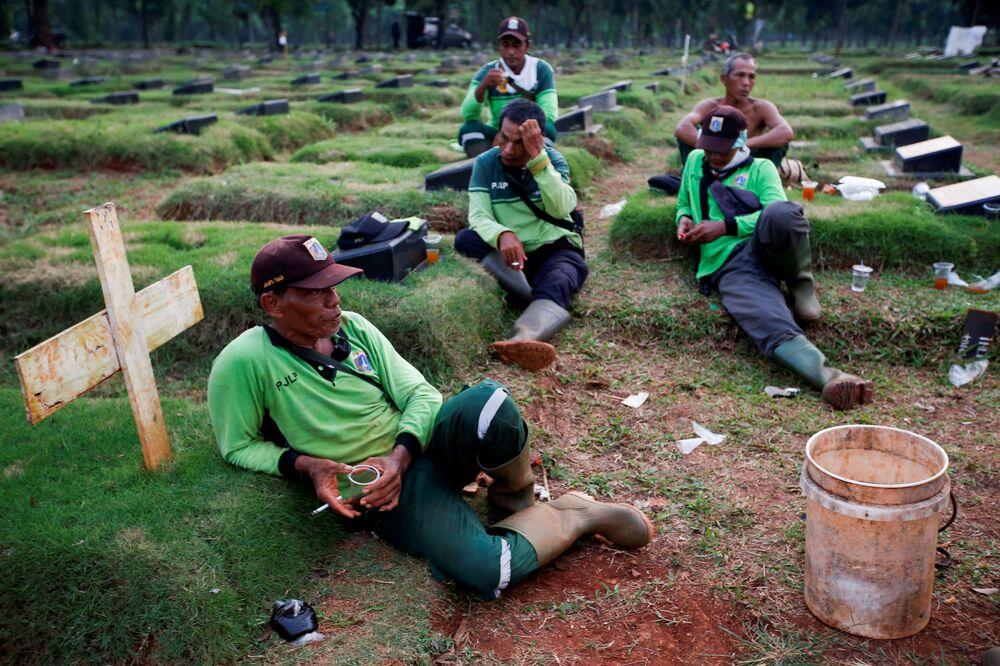 حفارو القبور خلال استراحة، وهم ينتظرون توابيت جديدة في مجمع مقبرة لضحايا فيروس التاجي (كوفيد-19) في جاكرتا، إندونيسيا 22 أبريل  2020.