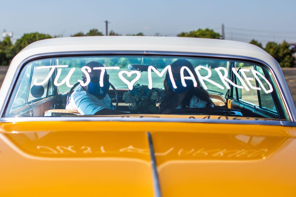 فيليب هيرنانديز (يسار) ومارسيلا بيرو يتوقفان لالتقاط صورة لهما داخل سيارتهم، في موقف سيارات مركز هوندا بعد أن تزوجوا من قبل كاتب مقاطعة في 21 أبريل 2020 في أنهايم، كاليفورنيا.