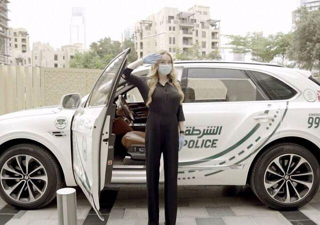 الممثلة الأمريكية ليندسي لوهان بالقرب من سيارة الشرطة الإماراتية