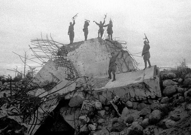 صور من أرشيف الحرب الوطنية العظمى (1941 - 1945) - جنود الجيش السوفيتي يقفون على حطام أحد السكنات العسكرية الألمانية لإطلاق النار، التي نسفها الجنود السوفييت. جبهة لينينغراد الحربية. 1944