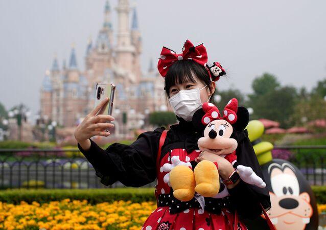 زائرة صينية ترتدي كمامة طبية وتلتقط صورة سيلفي في يوم إعادة افتتاح مدينة ديزني لاند في شنغهاي، الصين، 11 مايو/ أيار 2020