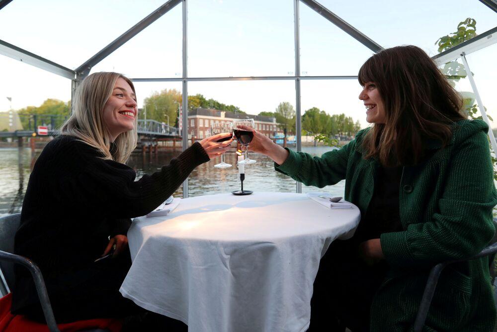 عارضات يقدمن نموذجا للزبائن وأفراد أسرة في مطعم، حيث يقام تجربة خدمة تقديم الأطباق والمشروبات إلى الأفراد في الدفئية الصحية، في إطار الإجراءات الوقائية  الآمنة بعد الخروج من الحجر الصحي بالتدريج، يستطيع فيه الضيوف تناول الطعام في أمستردام، هولندا، 5 مايو/ أيار 2020.