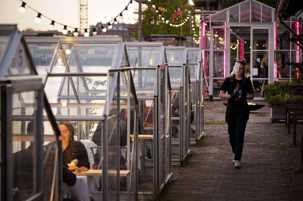 نوادل مطعم يقومون بدور الزبائن في تجربة لـ الدفئية الصحية، في إطار الإجراءات الوقائية  الآمنة بعد الخروج من الحجر الصحي بالتدريج، يستطيع فيه الضيوف تناول الطعام في أمستردام، هولندا، 5 مايو/ أيار 2020.