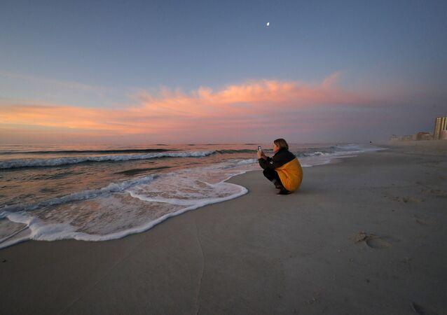 فتاة على شاطئ أورنج بيتش المطلة على خليج المكسيك، الولايات المتحدة 13 مارس 2020