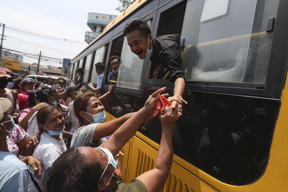 سجين يُخرج نفسه من  نافذة حافلة لمصافحة أفراد عائلته بعد إطلاق سراحه من سجن إنسين في إطار عفو رئاسي في يانغون، ميانمار، 17 أبريل 2020. وأطلقت ميانمار سراح ما يقارب من 25000 سجين بموجب عفو رئاسي بمناسبة الأسبوع الاحتفالي برأس السنة القمرية التقليدية.