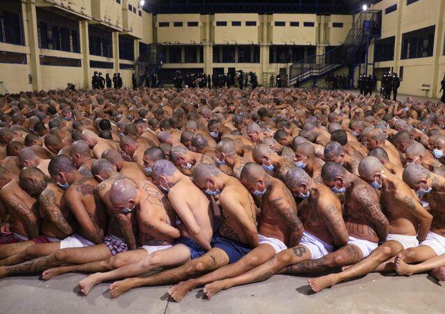 في هذه الصورة التي نشرها المكتب الصحفي لرئاسة السلفادور، يظهر فيها السجناء خلال عملية أمنية تحت مراقبة الشرطة في سجن إيزالكو في سان سلفادور في 25 أبريل 2020. حيث قامت السلطات بحشر السجناء معا، وإن كانوا يرتدون الكمامات، في ساحات السجن أثناء تفتيش الزنازين. وكان قد أمر الرئيس ناييب بوكيلي بالحملة بعد مقتل أكثر من 20 شخصًا في البلاد، وأشارت المخابرات المحلية إلى أن الأوامر (بالقتل) جاءت من قادة العصابات المسجونين.