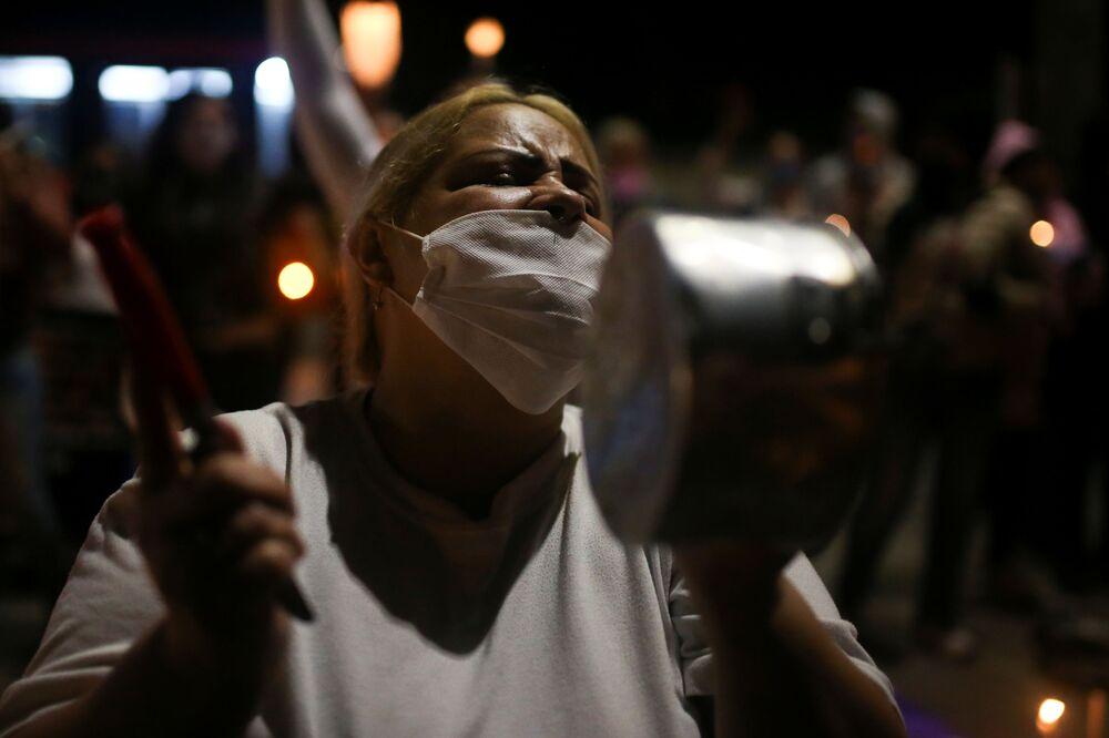 امرأة ترتدي كمامة وتدق على قدر من الألومنيوم خلال احتجاجات لأقارب السجناء أمام سجن لا بيكوتا ضد الاكتظاظ في سجون البلاد، وسط تفشي مرض الفيروس التاجي (كوفيد-19) في بوغوتا، كولومبيا  12 مايو  2020.