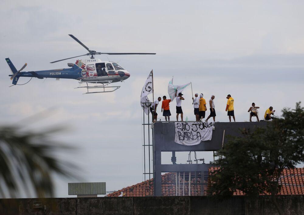 سجناء على سطح سجن بوراكيكوارا بينما تحلق مروحية تابعة للشرطة خلال أعمال شغب، بعد تفشي مرض فيروس كورونا (كوفيد-19) في مانواس، البرازيل، 2 مايو 2020