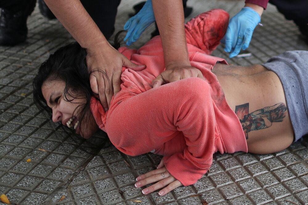 ضباط شرطة يعتقلون قريبًا للسجناء، خارج سجن ديفوتو خلال أعمال شغب تطالب بإجراءات صحية ضد انتشار مرض فيروس كورونا (كوفيد-19)، في بوينس آيرس، الأرجنتين، 24 أبريل 2020.