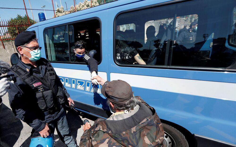 متظاهر على كرسي متحرك يرتدي كمامة يحاول لمس يد امرأة احتجزتها الشرطة المحلية خلال مظاهرة خارج سجن ربيبا، للمطالبة بظروف صحية أفضل للسجناء داخل السجن مع استمرار انتشار فيروس التاجية (كوفيد-19)، في روما، إيطاليا 16 أبريل 2020.