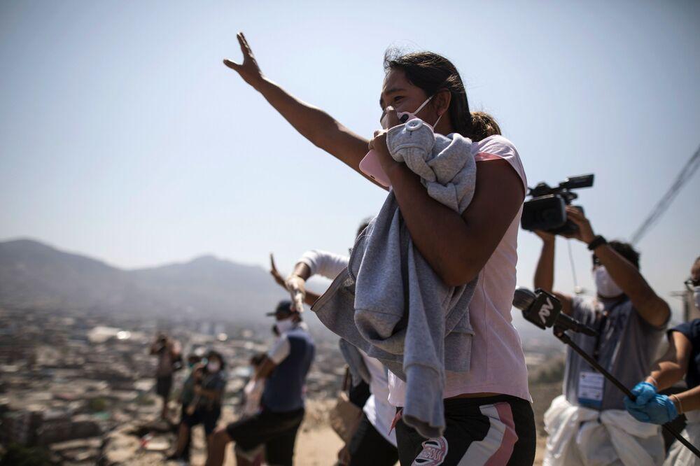 من أعلى التل، امرأة تنادي على أحد أقاربها، وهو سجين في سجن لوريغانشو أثناء احتجاج في السجن في ليما، بيرو، 28 أبريل 2020. حيث يشكو السجناء من أن السلطات لا تفعل ما يكفي لمنع انتشار مرض الفيروس التاجي كوفيد-19 داخل السجن.