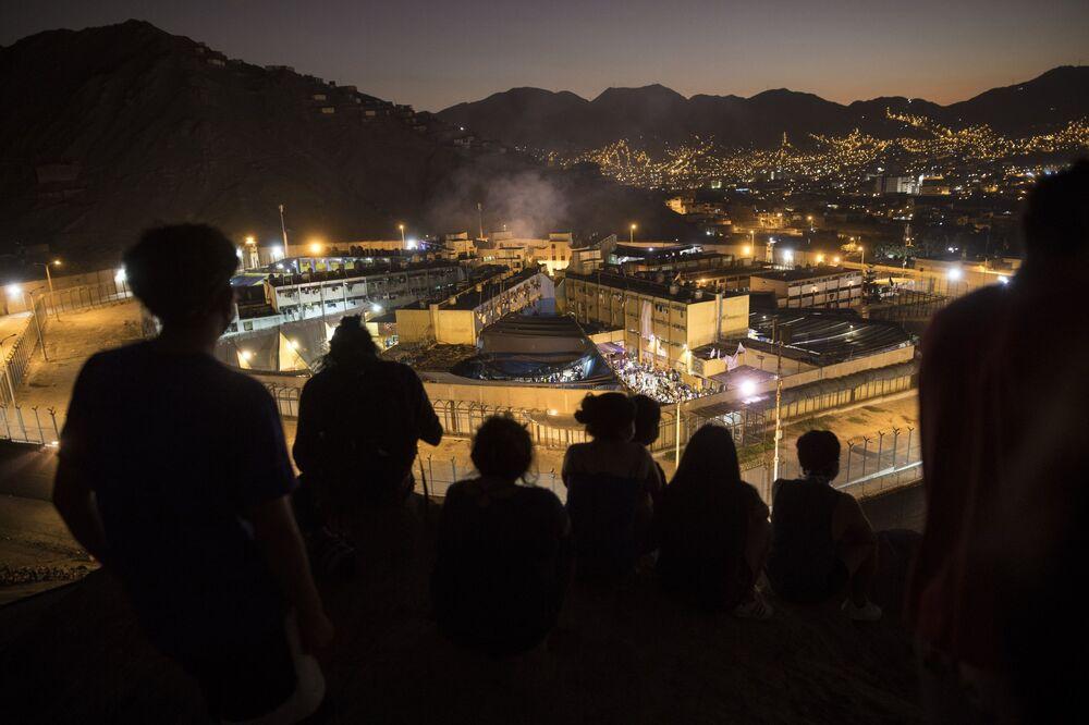 أقارب يقفون عل تل ينظرون إلى سجن كاسترو كاسترو خلال أعمال شغب بداخل السجن في ليما، بيرو 27 أبريل 2020. أفادت وكالة السجون في بيرو أن ثلاثة سجناء ماتوا لأسباب  غير معروفة لا تزال قيد التحقيق، بعد أعمال شغب في سجن ميغيل كاسترو كاسترو في ليما. يشكو السجناء من أن السلطات لا تفعل ما يكفي لمنع انتشار الفيروس التاجي كورونا داخل السجن.