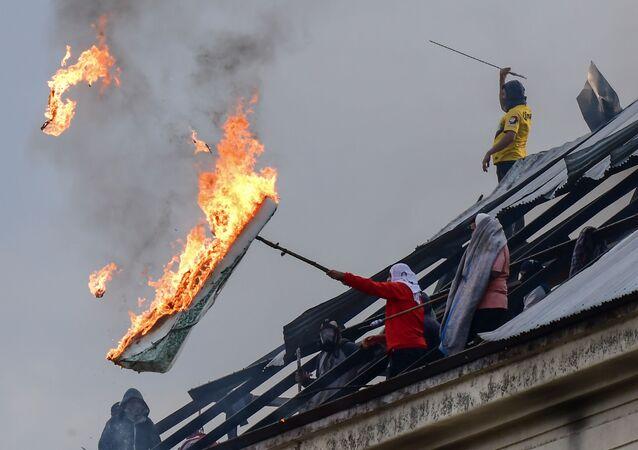 سجناء يحرقون فراشًا في سجن فيلا ديفوتو خلال أعمال شغب تطالب باتخاذ إجراءات لمنع انتشار المرض الفيروسي التاجي كوفيد-19، بعد الإبلاغ عن حالة إصابة داخل مركز الاعتقال، في بوينس آيرس، الأرجنتين في 24 أبريل 2020.
