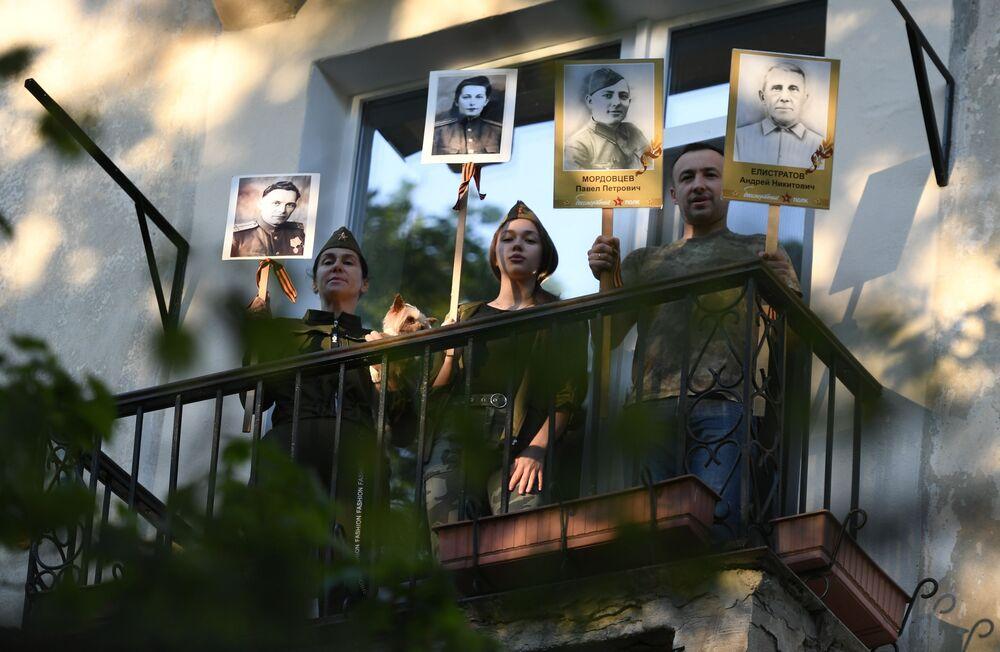 مواطنون من القرم الروسية يشاركون في فعالية الفوج الخالد من المنزل وسط العزل الذاتي، بمناسبة إحياء الذكرى الـ75 للانتصار على ألمانيا النازية في الحرب الوطنية العظمى  (1941-1945)