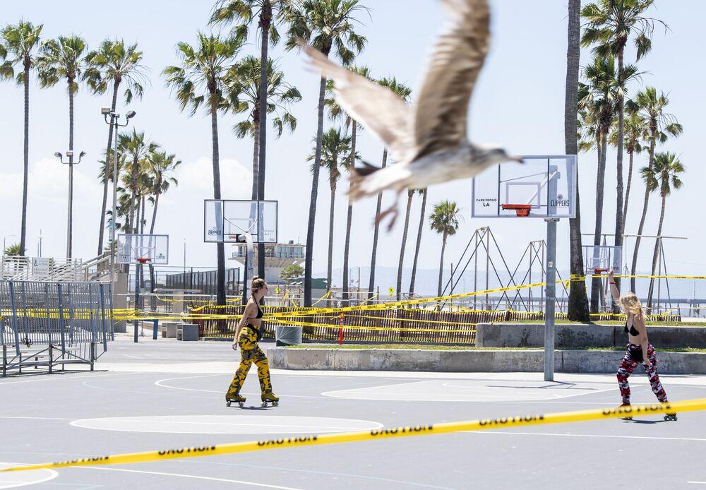 شاطئ فينيسيا في كاليفورنيا، أول يوم سمحت فيه مقاطعة لوس أنجلس بإعادة فتح الشواطئ بعد إغلاقه لمدة دامت ستة أسابيع في إطار منع تفشي فيروس كورونا (كوفيد-19)، في 13 مايو / أيار 2020. - لا تسمح المقاطعة إلا بأنشطة مثل الركض، والسباحة، والسباحة، والركوب الأمواج بينما منعت الاستجمام تحت الشمس ولعب الكرة الطائرة.