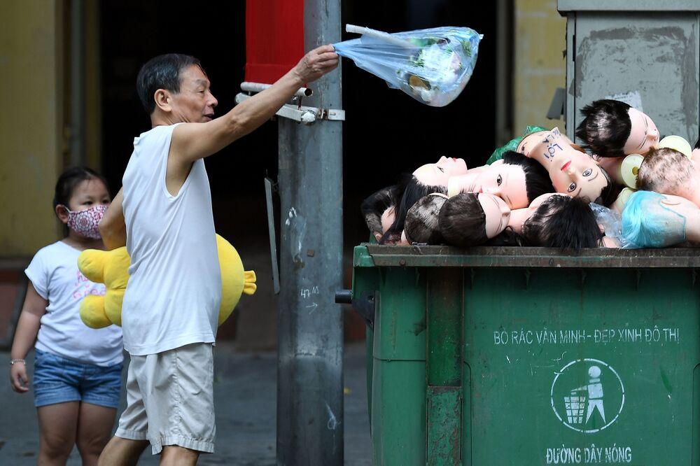 رجل يلقي القمامة في صندوق مليء برؤوس المانيكان في هانوي، فيتنام 7مايو / أيار 202