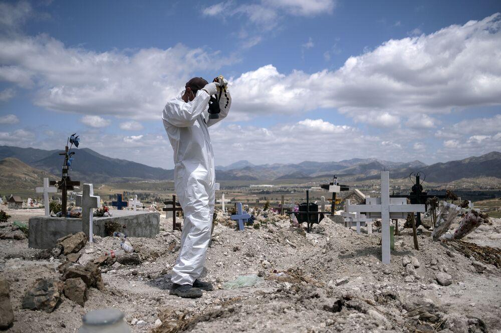 حفار القبور يستعد لدفن ضحيتي كورونافي تيخوانا، المكسيك 12 مايو/ أيار 2020