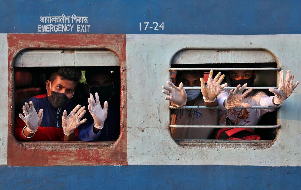 يلوح أشخاص يرتدون قفازات من القطار لدى وصولهم من ولاية تاميل نادو الجنوبية، وذلك بعد إعادة فتح محدود لخط السكك الحديدية في الهند بعد إغلاق لمدة سبعة أسابيع تقريبًا لإبطاء انتشار مرض (كوفيد-19)، في محطة سكة الحديد هوراه جانكشون على مشارف كلكتا، الهند  12 مايو 2020.