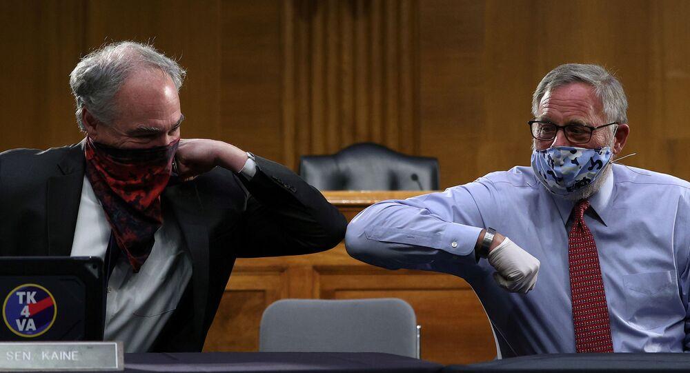 عضو مجلس الشيوخ الأمريكي ريتشارد بور (يمين) والسيناتور تيم كين (يسار) يرحبان ببعضهما بالكوع أمام لجنة مجلس الشيوخ للصحة والتعليم والعمل والمعاشات أثناء جلسة بشأن مرض فيروس كورونا (كوفيد- 19)، في واشنطن، الولايات المتحدة، 12 مايو 2020.