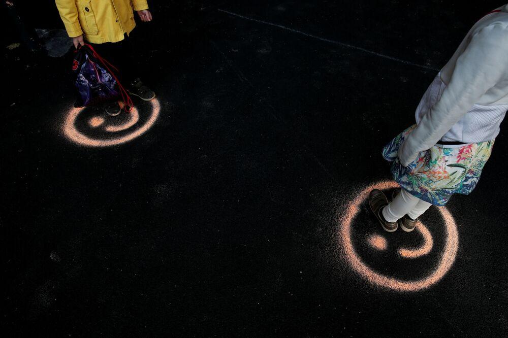 تلاميذ المدارس يقفون على علامات وجه مبتسم للحفاظ على التباعد الاجتماعي في فناء مدرسة ابتدائية، بهد الإعلان عن إعادة افتتاحها في باريس، حيث عاد جزء صغير من الأطفال الباريسيين إلى مدارسهم بقواعد جديدة أثناء تفشي مرض فيروس التاجي (كوفيد- 19) في فرنسا، 14 مايو 2020.
