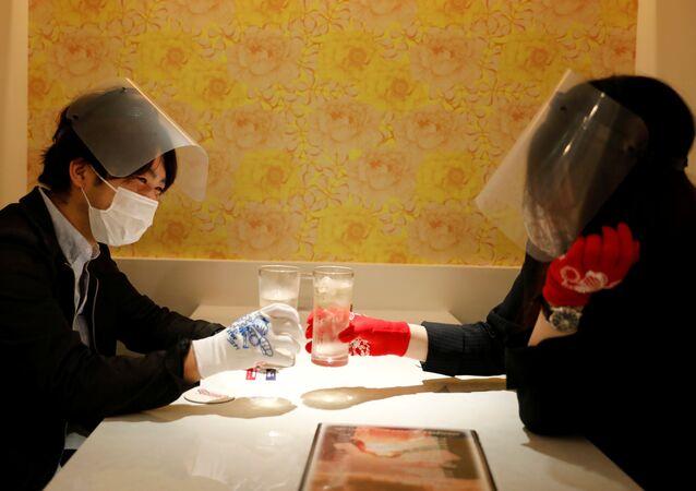 نادلات يرتدين كمامات طبية، وأقنعة واقية، وقفازات لمنع الإصابة بعدوى مرض فيروس كورونا (كوفيد-19)، يخدمن الزبائن في مطعم Cheers One في طوكيو، اليابان 11 مايو / أيار 2020.