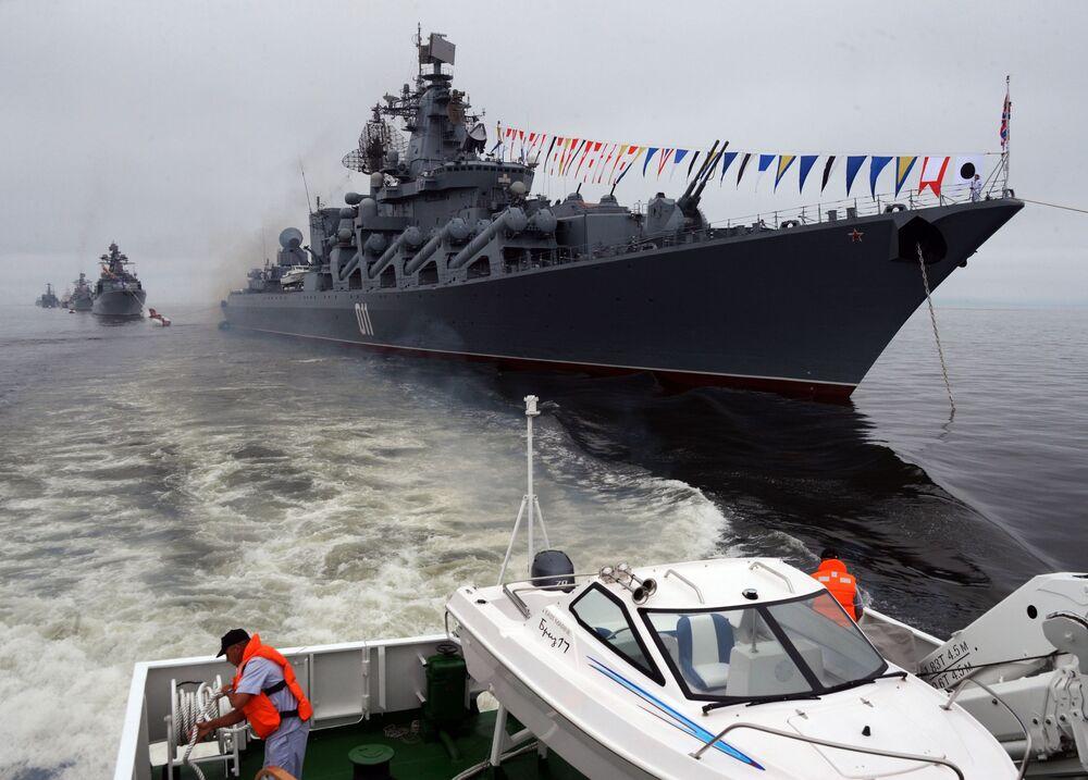 أعلام معهد ناخيموف لقوات البحرية الروسية من طراد الصواريخ فارياغ في مراسم احتفالية بيوم البحرية في فلاديفوستوك الروسية.