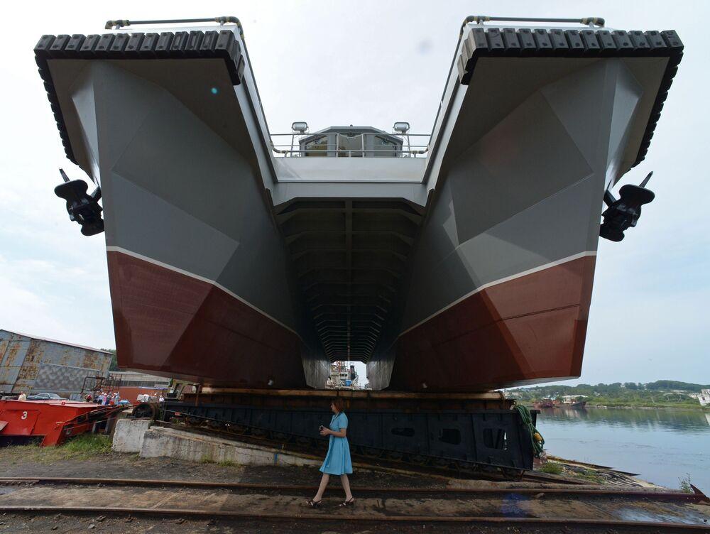 امرأة تقف أمام قارب مشروع 23370 متعدد المهام بمصنع ليفادييسكي لإصلاح وبناء السفن، مصمم لطاقم الإنقاذ التابع لأسطول المحيط الهادئ، قبل بدء مراسم الإنزال في إقليم بريمورسكي كراي