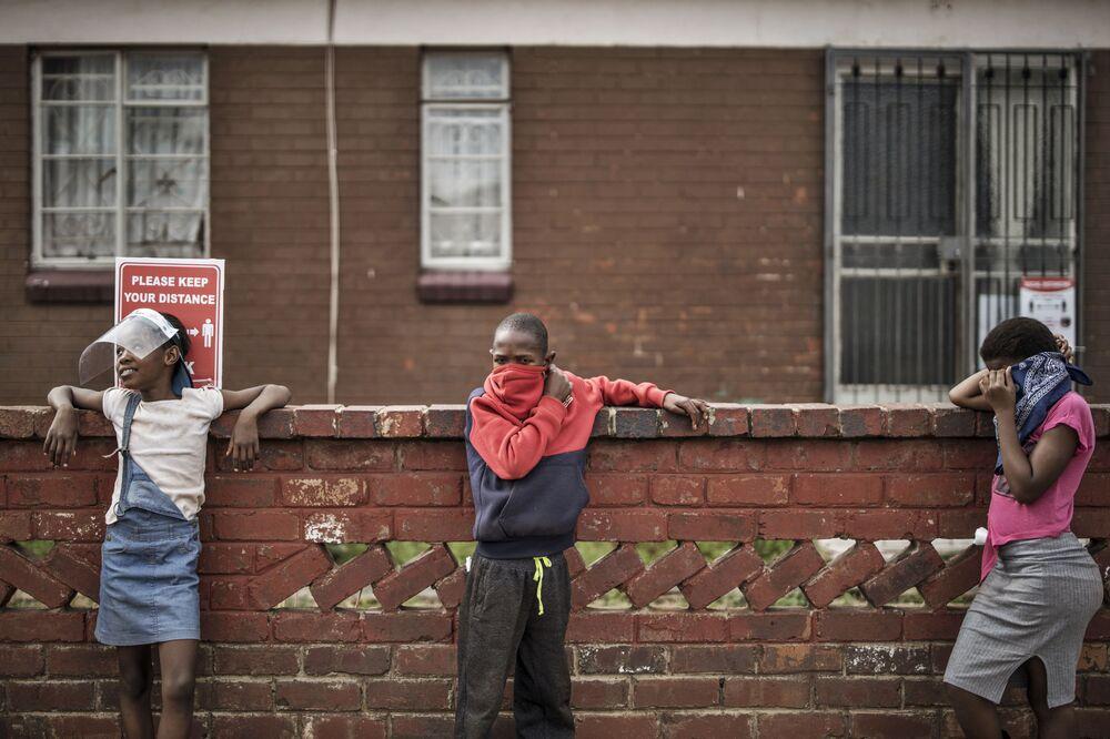 أطفال يحافظون على مسافة التباعد الاجتماعي أثناء وقوفهم في طابور بانتظار الطعام الذي تنظمه الجمعية الخيرية الشعبية الجوع لا دين له، في ويستبري، جوهانسبرغ، 19 مايو 2020