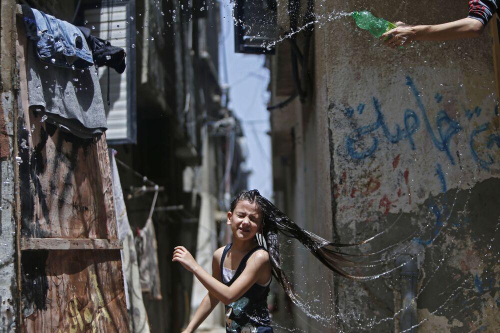 صبي يسكب الماء على رأسه طفلة لتخفيف الحر عنها، خلال موجة جو حار في مخيم البريج للاجئين وسط قطاع غزة، وسط جائحة  كوفيد-19 ، 19 مايو 2020. يذكر أن موجة حر شديد ضربت العديد من دول منطقة الشرق الأوسط.