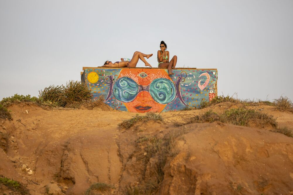 تستمتع النساء بغروب الشمس على البحر الأبيض المتوسط، حيث بلغت درجات الحرارة 38 درجة مئوية في الخضيرة، حيفا، إسرائيل، 16 مايو 2020. بدأت إسرائيل في تخفيف القيود تدريجيًا في أوائل مايو مع قرار بفتح الشواطئ أمام الزوار في وقت سابق من هذا الأسبوع.