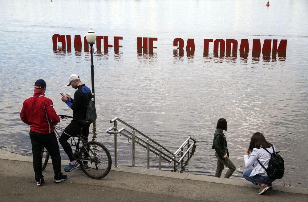 سكان مدينة بيرم الروسية أمام النموذج الفني السعادة قاب قوسين أو أدنى، غمرتها المياه نتيجة ارتفاع منسوب مياه نهر كاما.