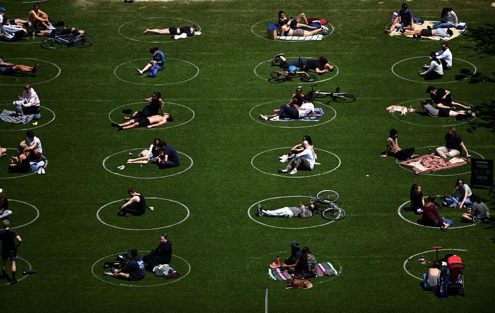 شوهد الناس يحافظون على التباعد الاجتماعي في الدوائر البيضاء المخصصة لهم بالجلوس في حديقة دومينو، في إكار تخفيف القيود المفروضة بسبب جائحة كورونا في حي بروكلين في مدينة نيويورك، 17 مايو 2020